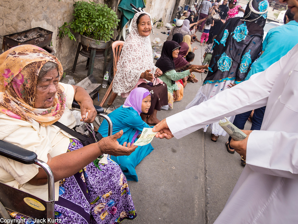 """08 AUGUST 2013 - BANGKOK, THAILAND: A man leaving Haroon Mosque for Eid al-Fitr gives money to a woman waiting for zakat, or alms. Giving alms on Eid is an important part of the tradition of the day. Eid al-Fitr is the """"festival of breaking of the fast,"""" it's also called the Lesser Eid. It's an important religious holiday celebrated by Muslims worldwide that marks the end of Ramadan, the Islamic holy month of fasting. The religious Eid is a single day and Muslims are not permitted to fast that day. The holiday celebrates the conclusion of the 29 or 30 days of dawn-to-sunset fasting during the entire month of Ramadan. This is a day when Muslims around the world show a common goal of unity. The date for the start of any lunar Hijri month varies based on the observation of new moon by local religious authorities, so the exact day of celebration varies by locality.      PHOTO BY JACK KURTZ"""