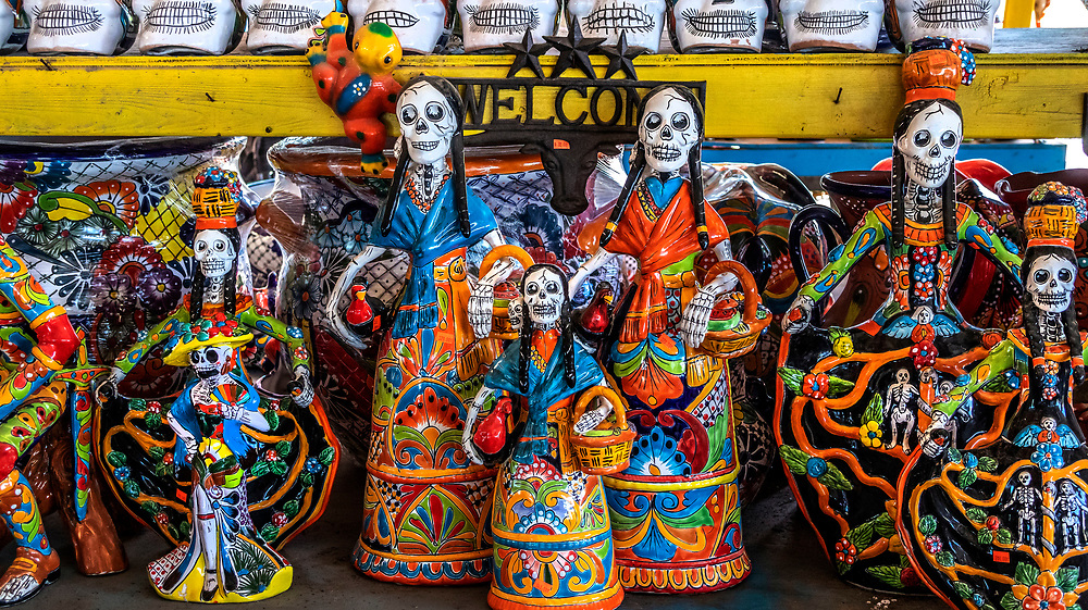 Pottery day of the dead skeletons on sale at a roadside shop, Texas, USA