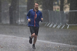 © Licensed to London News Pictures. 01/10/2021. London, UK. A man jogs during heavy rain in Greenwich Park in South East London. Rain showers are forecasted to continue in parts of London and South East England for the rest of the week.  Photo credit: George Cracknell Wright/LNP