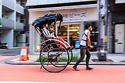 A pulled rickshaw or jinrikisha transports tourists  around the Sensoji Buddhist temple and the historic Asakusa neighborhood in Tokyo, Japan.