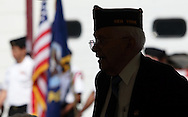 Middletown, NY  -  A veteran standing under a tent is seen in silhouette before the start of a  Memorial Day ceremony  on May 25, 2009.