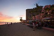 """Sunset at Waikiki Beach. The Mai Tai bar at the historic Royal Hawaiian Hotel, also known as the """"Pink Lady""""."""