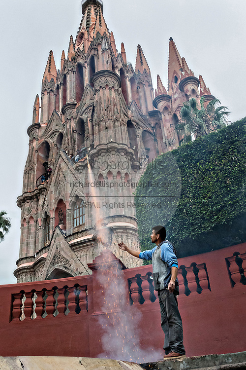 A fireworks worker sets off a bottle rocket in front of the Parroquia San Miguel Archangel church during the week long fiesta of the patron saint Saint Michael September 24, 2017 in San Miguel de Allende, Mexico.