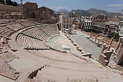 Wide-angle side view of the Roman Amphitheatre at Cartagena (Carthago Nova) from above, showing the surrounding mountains in the background.