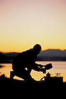 A young woman makes backcountry coffee on the shore of Jackson Lake in Grand Teton National Park, Wyoming.