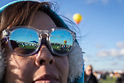 Hot air balloons are reflected in the glasses of Hannah Gillreath at the AARP Block Party at the Albuquerque International Balloon Fiesta in Albuquerque New Mexico USA on Oct. 8th, 2018.