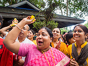 31 AUGUST 2014 - SARIKA, NAKHON NAYOK, THAILAND: Women throw marigolds at Ganesh to honor him during the Ganesh Festival at Shri Utthayan Ganesha Temple in Sarika, Nakhon Nayok. Ganesh Chaturthi, also known as Vinayaka Chaturthi, is a Hindu festival dedicated to Lord Ganesh. It is a 10-day festival marking the birthday of Ganesh, who is widely worshiped for his auspicious beginnings. Ganesh is the patron of arts and sciences, the deity of intellect and wisdom -- identified by his elephant head. The holiday is celebrated for 10 days, in 2014, most Hindu temples will submerge their Ganesh shrines and deities on September 7. Wat Utthaya Ganesh in Nakhon Nayok province, is a Buddhist temple that venerates Ganesh, who is popular with Thai Buddhists. The temple draws both Buddhists and Hindus and celebrates the Ganesh holiday a week ahead of most other places.    PHOTO BY JACK KURTZ