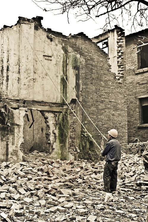 CHONGQING, CHINA - DEC 29, 2010: A worker uses ropes to tear down a wall in Dan Zi Shi.