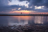 A pool of water on South Beach in South Haven reflects a warm glow of light remaining after the sun had set