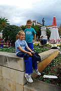 Two children (9 years old, 5 years old) in town square (Kacicev trg), with statue of friar Andrija Kacic-Miosic in background. Makarska, Croatia