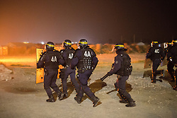 "© Licensed to London News Pictures . 23/10/2016 . Calais , France . Riot police charge residents at the Calais migrant camp known as "" The Jungle "" , in Northern France , as residents set fires , on the evening before the start of the eviction and destruction of the camp . Photo credit: Joel Goodman/LNP"