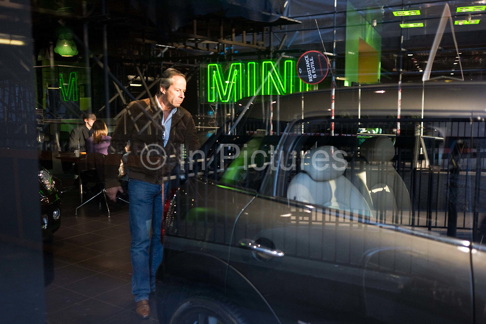 An interested potential buyer looks over a car at a Mini car dealership in London's Park Lane. With sunlight streaming into the otherwise darkened design of the car showroom, the man looks over a Mini Cooper model with the prominent word Mini in green letters on the ceiling. The Mini is a small car that was made by the British Motor Corporation (BMC) and its successors from 1959 until 2000. The original is considered a British icon of the 1960s and its space-saving front-wheel-drive layout (which allowed 80% of the area of the car's floor pan to be used for passengers and luggage) influenced a generation of carmakers. In 1999 the Mini was voted the second most influential car of the 20th Century, behind the Ford Model T.