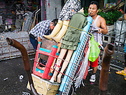 30 MAY 2013 - BANGKOK, THAILAND:  A vendor tears down his market stall in Bobae Market in Bangkok. Bobae Market is a 30 year old famous for fashion wholesale and is now very popular with exporters from around the world. Bobae Tower is next to the market and  advertises itself as having 1,300 stalls under one roof and claims to be the largest garment wholesale center in Thailand.    PHOTO BY JACK KURTZ