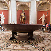 The Sala Rotonda room in the Museo Pio Clementino museum contains several notable statues and an incredible mosaic floor. A gilded-bronze Hercules and a large basin composed of a single piece red porphyry stone are main draws.