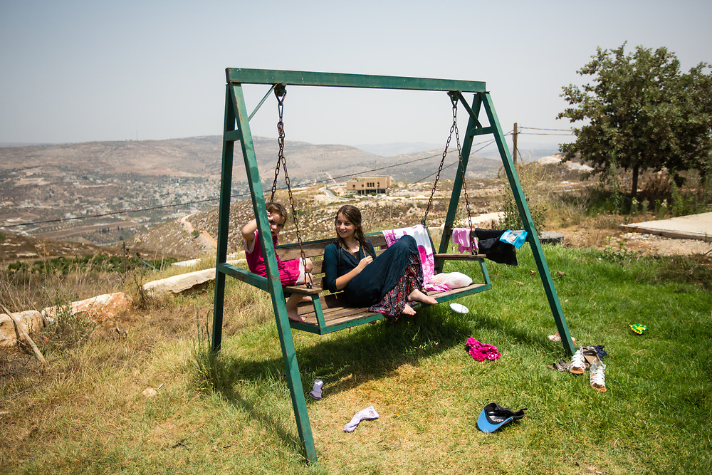 Backdropped by a view of the West Bank hills, Jewish Israeli girls sit on a swing, during a hot summer day in the West Bank Jewish settlement of Yitzhar, south of the Palestinian West Bank city of Nablus, on August 5, 2015.