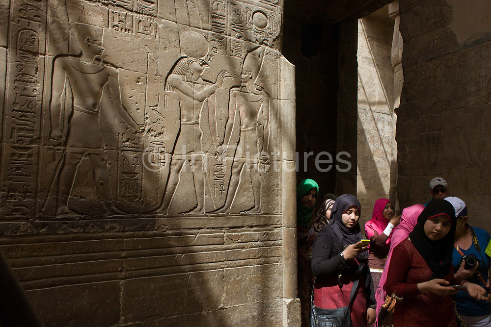 Egyptian women under sunlit hieroglyphs in the dark recesses of the ancient Egyptian Luxor Temple, Nile Valley, Egypt. According to the country's Ministry of Tourism, European visitors to Egypt is down by up to 80% in 2016 from the suspension of flights after the downing of the Russian airliner in Oct 2015. Euro-tourism accounts for 27% of the total flow and in total, tourism accounts for 11.3% of Egypt's GDP. The temple was built by Amenhotep III, completed by Tutankhamun then added to by Rameses II. Towards the rear is a granite shrine dedicated to Alexander the Great  and in another part, was a Roman encampment. The temple has been in almost continuous use as a place of worship right up to the present day.