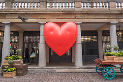 """© Licensed to London News Pictures. 14/02/2018. LONDON, UK. A giant chubby heart balloon is seen at Covent Garden as part of """"Chubby Hearts Over London"""",  a design project conceived by Anya Hindmarch.  Supported by the Mayor of London, the British Fashion Council and the City of Westminster giant chubby heart balloons will be suspended over (and sometimes squashed within) London landmarks as a declaration of love to the city starting on Valentine's Day and continuing throughout London Fashion Week.   Photo credit: Stephen Chung/LNP"""