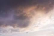 A jet airliner climbs away into the distance after taking-off in pink afternoon skies above London's Heathrow Airport.