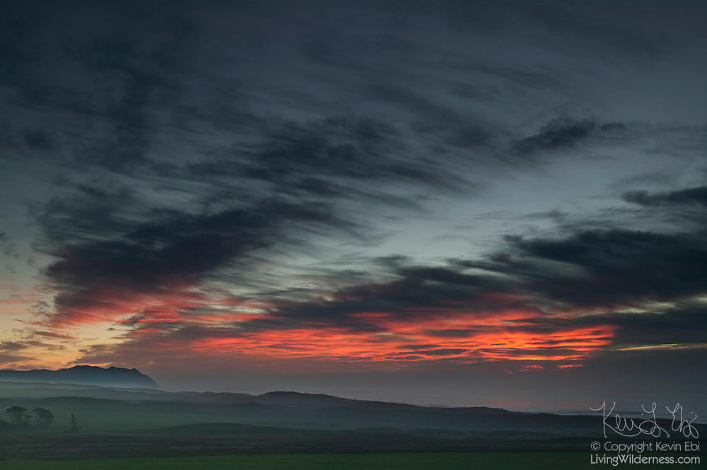 The setting sun colors approaching winter storm clouds over the Point Reyes National Seashore in northern California.