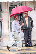 People rush use umbrella during a rainy weather in capital Tirana as electoral campaign rallies continue ahead of the upcoming general election in Tirana, Albania on Tuesday, June 23, 2009. Albanians will vote in the legislative elections on 28 June. (Photo by Vudi Xhymshiti)