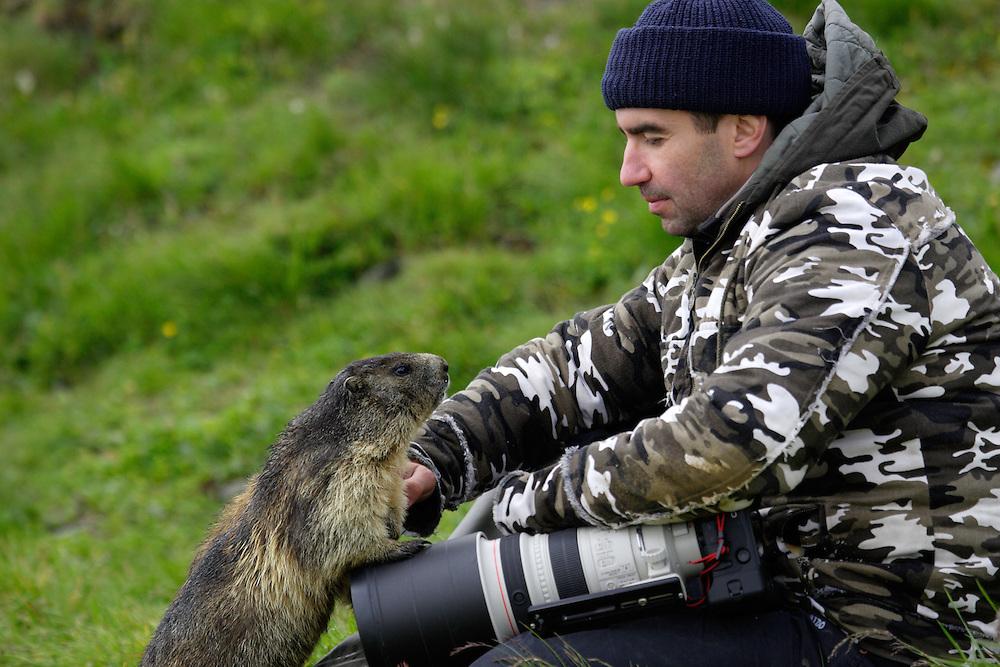 Photographer with marmot (model release 03/08/HTNP) Hohe Tauern National Park, Carinthia, Austria