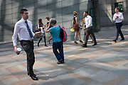 City workers walk along a pedestrian pavement at Broadgate in the City of London.