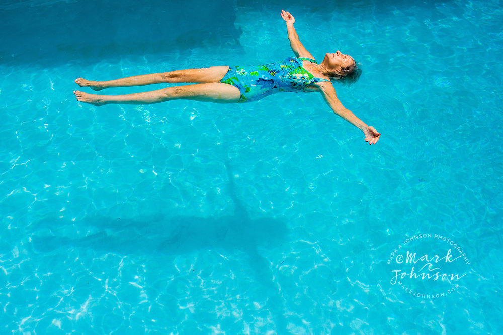 Senior woman floating on her back in a swimming pool ****Model Release available