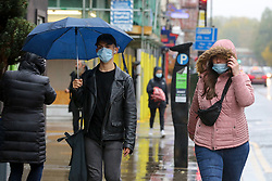 © Licensed to London News Pictures. 21/10/2020. London, UK. Members of the public wearing face coverings shelter from rain underneath umbrellas in north London. According to the Met Office, heavy rain and strong winds are forecast later today from Storm Barbara. Photo credit: Dinendra Haria/LNP