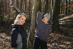 Man and woman doing stretching on fitness trail in nature