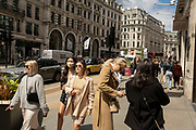 People out and about in the shopping district of Regent Street, some wearing face masks and others not on 26th May 2021 in London, United Kingdom. As the coronavirus lockdown continues its process of easing restrictions, more and more people are coming to the West End as more retail businesses open.