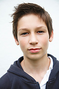 Portrait of teenage boy looking straight at camera informal clothes brown hair white wall background