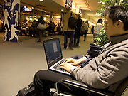 man working on his computer wail waiting in a public space