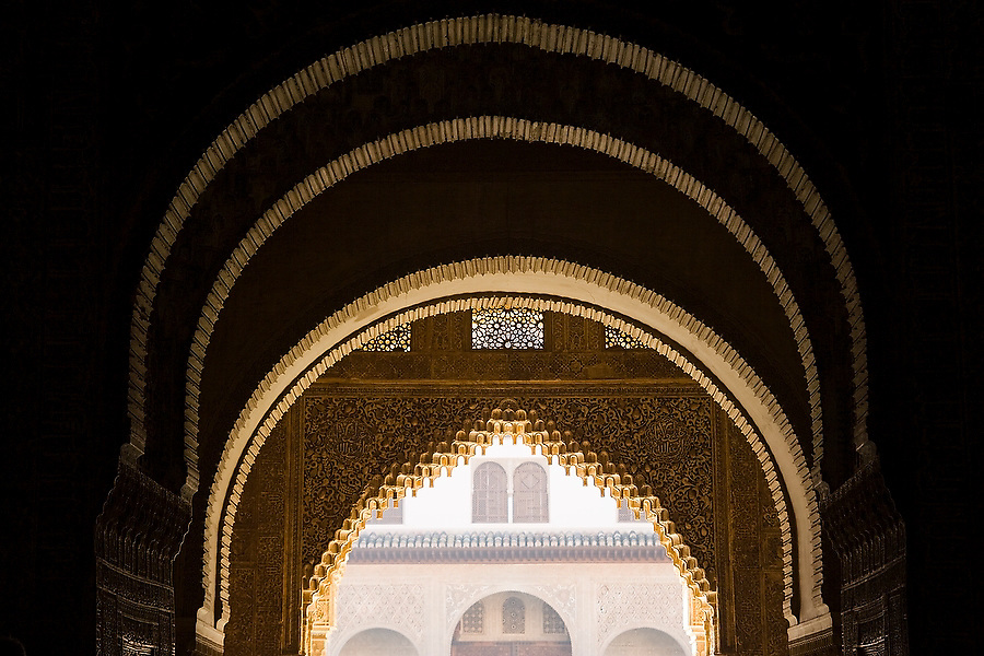 A series of decorative stone carved arches frame a doorway and building facade in the Casa Real complex of the 14th century palace of La Alhambra, Granada, Andalusia, Spain.