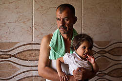© Licensed to London News Pictures. Hamdaniyah, Iraq. 25/07/2014. Christian refugee Ra'id Samir Kamal (45), formerly a driver in Mosul, holds his five year old daughter, Rania, at the home they now share with 15 other members of their extended family in Hamdaniyah, Iraq. Samir left Mosul on Friday the 18th of July when Islamic State fighters issued an ultimatum to the city's Christian community. When the family left they were forced to pay a tax for their car, their son (19) was threatened at knifepoint to ensure they handed over all of their possessions including family photographs.<br /> <br /> Having taken over Mosul Iraq's second largest city in June 2014, fighter of the Islamic State (formerly known as ISIS) have systematically expelled the cities Christian population. Despite having been present in the city for more than 1600 years, Christians in the city were given just days to either convert to Islam, pay a tax for being Christian or leave; many of those that left were also robbed at gunpoint as they passed through Islamic State checkpoints.. Photo credit : Matt Cetti-Roberts/LNP