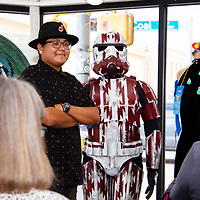 Artist Kirk Tom, 22, poses next to his Ké Trooper suit at the Best of Show Night at ART123 Gallery Tuesday evening.