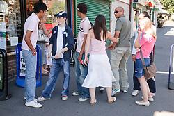 Young couple walking through teenage group.