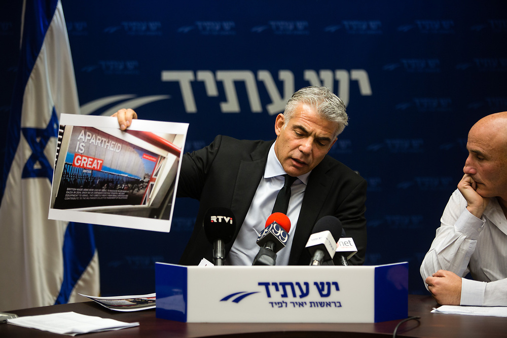 """Head of the Yesh Atid party, Israeli lawmaker Yair Lapid shows an image of anti-Israel posters put up in London's underground tube network earlier today as the annual """"Israel Apartheid Week"""" began, during a faction meeting at the Knesset, Israel's parliament in Jerusalem, on February 22, 2016."""