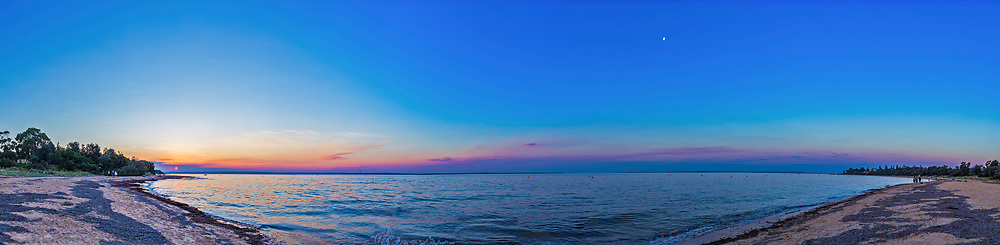 A 270° panorama of the setting Sun and waxing gibbous Moon over Western Port bay at Cowes on Philip Island near Melbourne, Victoria, Australia. <br /> <br /> The Sun is setting slightly north of due west, while the 9-day-old Moon sits in the northeast, at an angle of about 110° away from the Sun. <br /> <br /> This is a stitch of 15 panels taken with the 35mm lens oriented portait, and the Canon 6D camera. Stitched with PTGui with a lot of manual point registration required due to the lack of land area over many segments to align to.