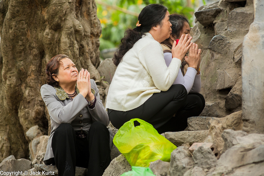 31 MARCH 2012 - HANOI, VIETNAM:   Vietnamese women pray at a shrine outside of Ngoc Son Temple, which was reportedly built during the Tran Dynasty (ca 1225) in the Old Quarter of Hanoi, Vietnam. The temple is dedicated to Tran Hung Dao, a Vietnamese national hero who defeated an invading Mongol army in the 13th century.      PHOTO BY JACK KURTZ