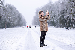 © Licensed to London News Pictures 28/12/2020, Cirencester, UK. A young woman stops to take pictures of the snow covered avenue of trees in Cirencester Park. Photo Credit : Stephen Shepherd/LNP