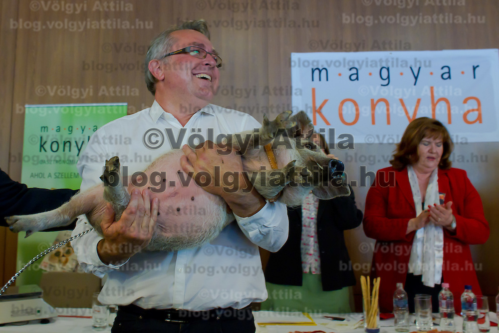 Laszlo Arpas celebrates his victory holding the piglet he won during the first ever ham slicing competition in Budapest, Hungary on May 9, 2012. ATTILA VOLGYI