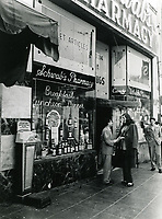 1944 Sidney Skolsky chats with Dorothy Ford in front of Schwab's Pharmacy