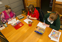 Amy Winters, Chelle Bergeron and Jeannette Perez chat and color during Hall Memorial Library's Adult Coloring Hour Monday evening.  (Karen Bobotas/for the Laconia Daily Sun)