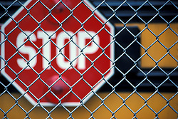Close up of wire fencing and yellow school bus stop sign insignia. CONCEPT STOCK PHOTOS