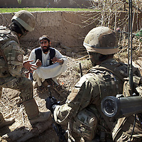 An Afghan interpreter assists British soldiers of 16 Air Assault Bde's elite BRF (Brigade Reconnaissance Force) as they question a local man whilst searching his compound as part of  an operation in the village of Kakaran in Helmand Province, Southern Afghanistan on the 14th of March 2011.