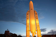 A full-scale mock-up of a multinational 50.5 meter-high European Space Agency's (ESA) Ariane 5 rocket is lit by floodlights in an early tropical evening at the main entrance to Guiana Space Centre, Kourou, French Guiana, South America. Glowing orange by the warm lighting, it makes an impressive model against the fading equatorial sky. Seen in scale, a lone human figure stands at the foot of the launcher that in reality, sends massive 8,000 kg payloads into orbit for a variety of communications and International Space Station purposes. Powered by Snecma-made Vulcain engines and boosted by Europropulsion solid motors, these rockets are launched from this facility on the Guiana coast. The building to the left are the CNES offices belong to the French Space Agency.
