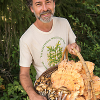 """Portrait of local """"mushroom man"""" Alan Muskat (model released) with a basket of chicken of the woods and honey mushrooms in the suburbs of Asheville, North Carolina."""