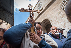 19 April 2019, Jerusalem: A man holds a cross, as thousands of Christians march the Via Dolorosa on Good Friday, marking the stations of the cross in the Jerusalem Old City, in memory of the path Jesus walked carrying his cross towards his crucifixion.