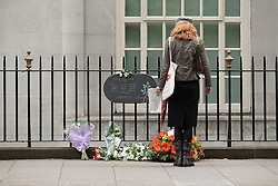 © Licensed to London News Pictures. LONDON, UK  07/07/11. A passer by looks at flowers laid at the Tavistock Square Bomb Memorial in London. The memorial remembers the 14 people who died on July the 7th 2005 at 09:47 when suicide bomber Hasib Hussain detonated his bomb on the Number 30 bus passing by the spot. The attack was one of 4 that were set off that day causing 56 deaths and hundreds of injuries. Please see special instructions for usage rates. Photo credit should read Matt Cetti-Roberts/LNP. Please see special instructions for usage rates. Photo credit should read Matt Cetti-Roberts/LNP