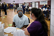 27 MARCH 2021 - DES MOINES, IOWA: JUSTIN PINKNEY talks to a nursing student about the COVID-19 vaccination he is about to get during a COVID-19 (Coronavirus) vaccination clinic at Corinthian Baptist Church in Des Moines, Saturday. The clinic was organized by Broadlawns Medical Center and the United Way and provided more than 1,100 shots to Des Moines area residents. The clinic was a part of an effort to reach communities of color in Iowa, who are vaccinated at rates below the state average.       PHOTO BY JACK KURTZ